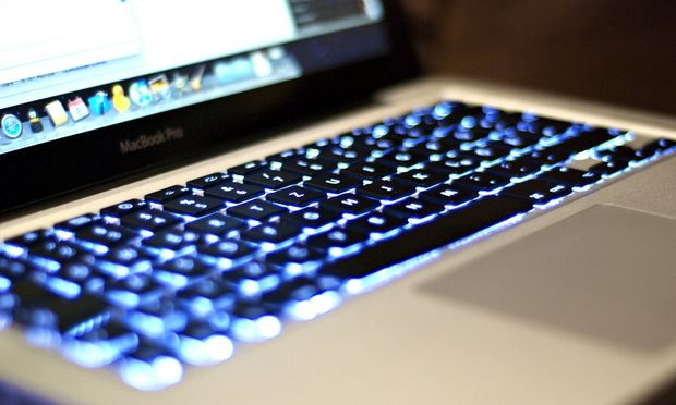 The keys of a Mac brand laptop glow with blue light