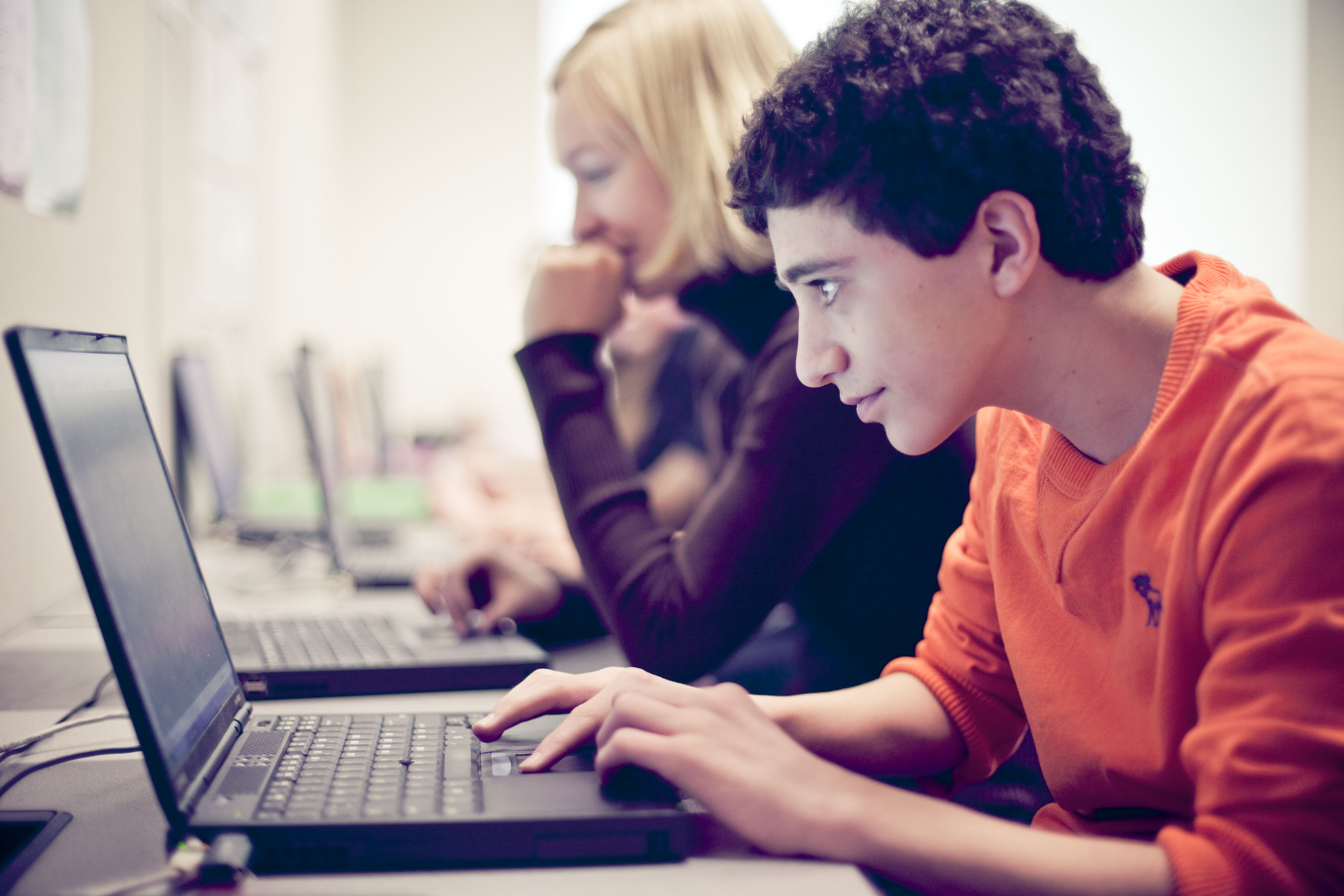 A young boy wearing an orange sweatshirt types on a laptop computer.
