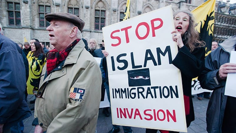 "At a protest in Belgium, a women carries a sign that reads ""Stop Islam Immigration Invasion."""