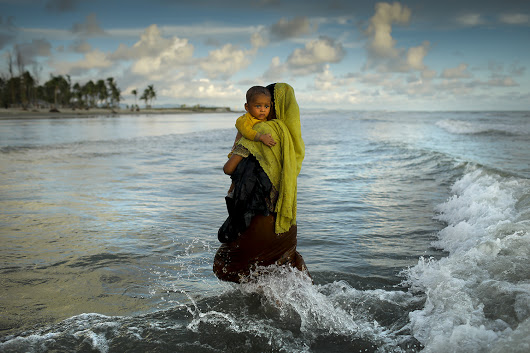 A mother and her child arrives from Myanmar by boat to Bangladesh