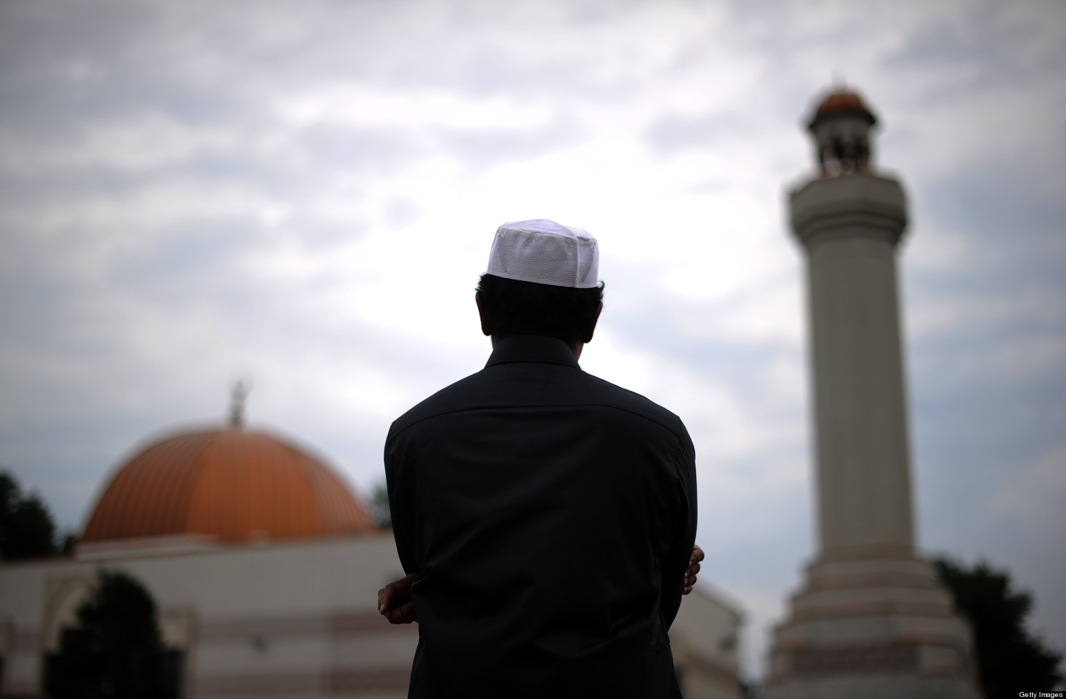 A man looks off at the distance toward a mosque, the image of which is blurred. The man wears a those and a taqiyah.