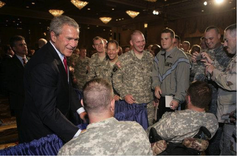 Former President George W.Bush stands next to officials in the U.S. army.