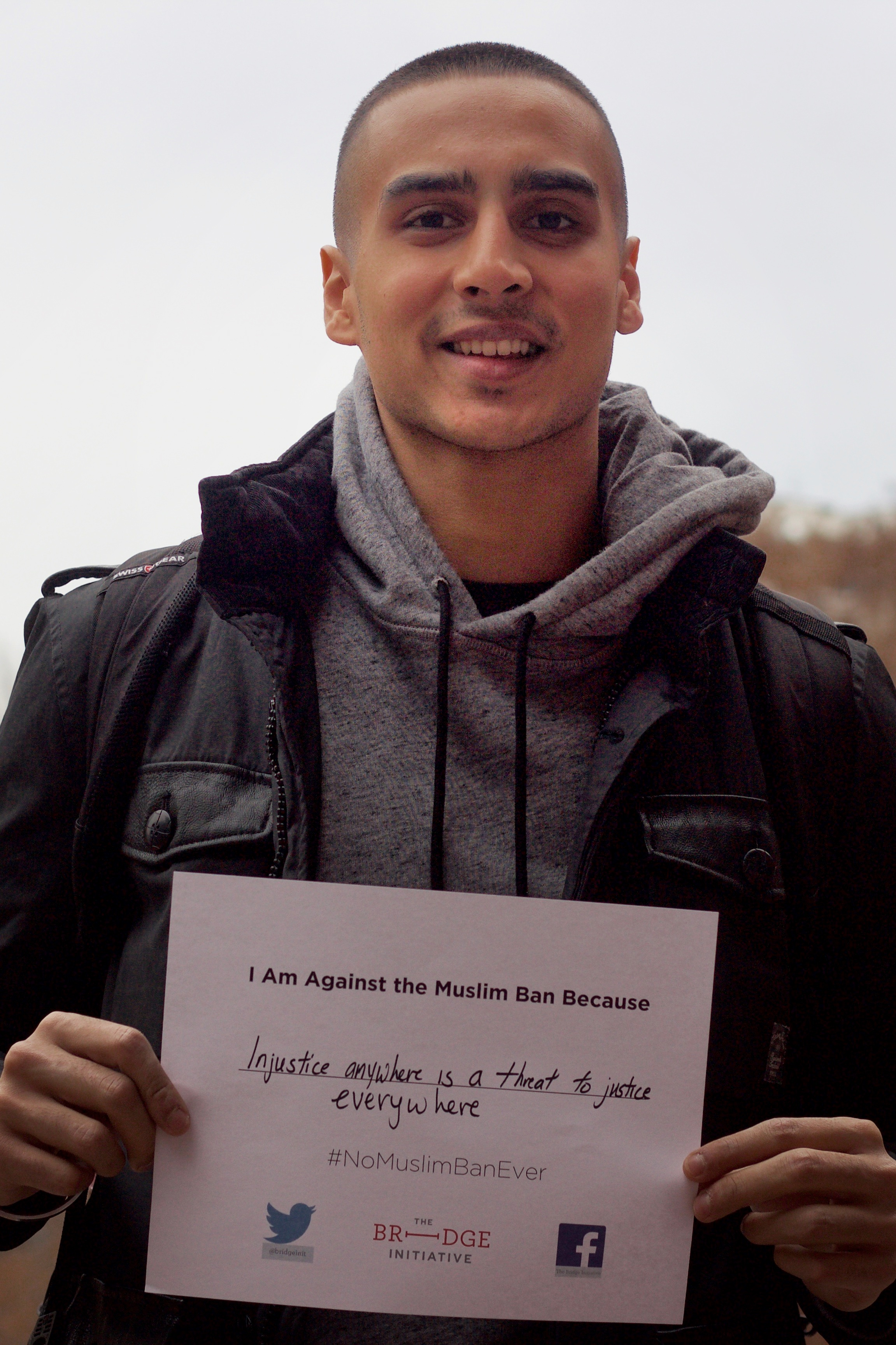 "person with short cropped, dark brown hair looks directly in the camera, smiling. The person, who is wearing a grey-colored sweatshirt and black jacket, hold a sign that reads, ""I am against the Muslim Ban because injustice anywhere is a threat to justice everywhere."" In the background is an overcast sky and a red-brick building."
