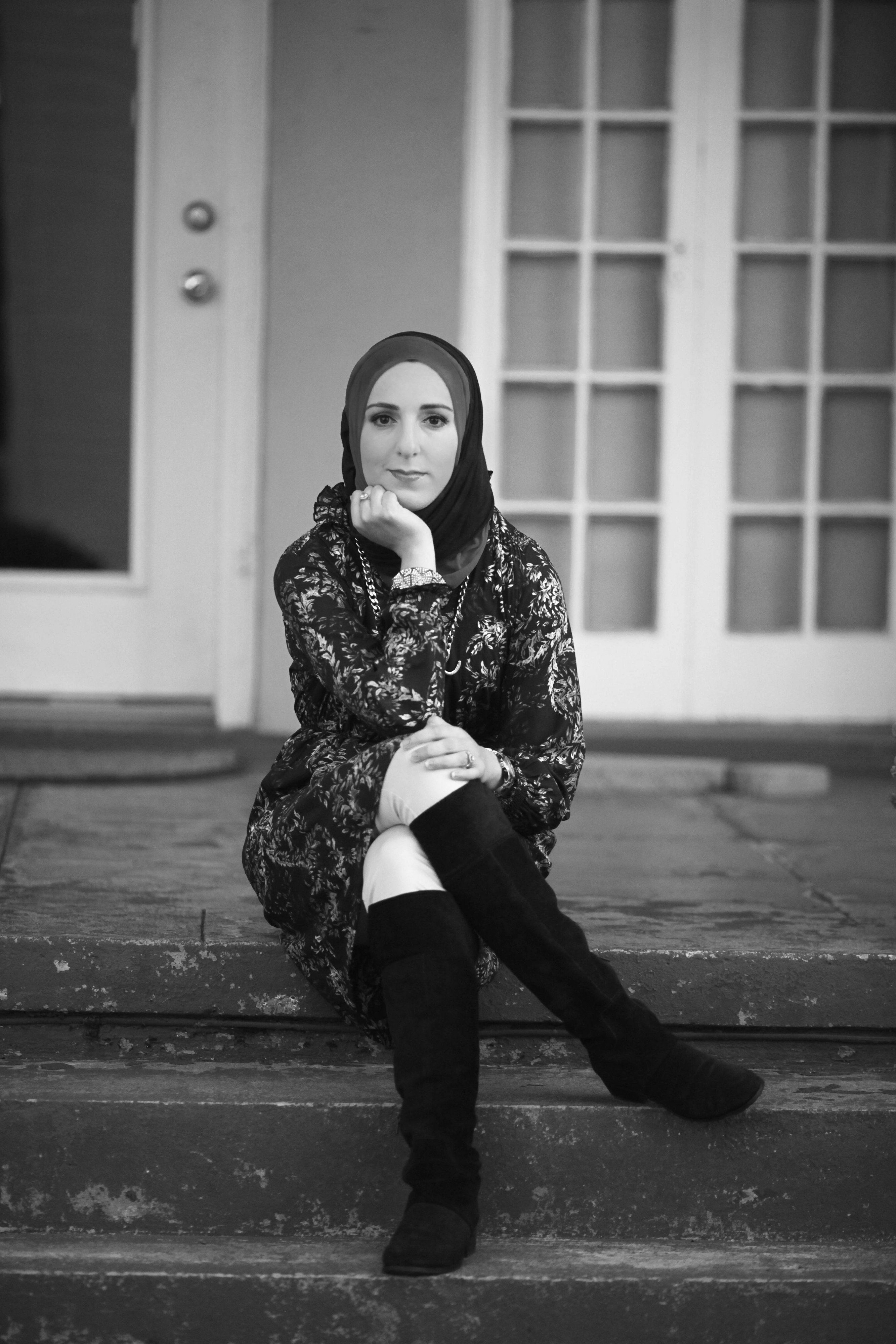 black-and-white photo of a person seated on steps leading up to a house. The person wears knee-high, black-colored boots, light-colored pants, a floral-patterned dress/tunic, a headscarf and a necklace, bracelet and ring. The person looks at the camera, with legs crossed and chin resting in hand.