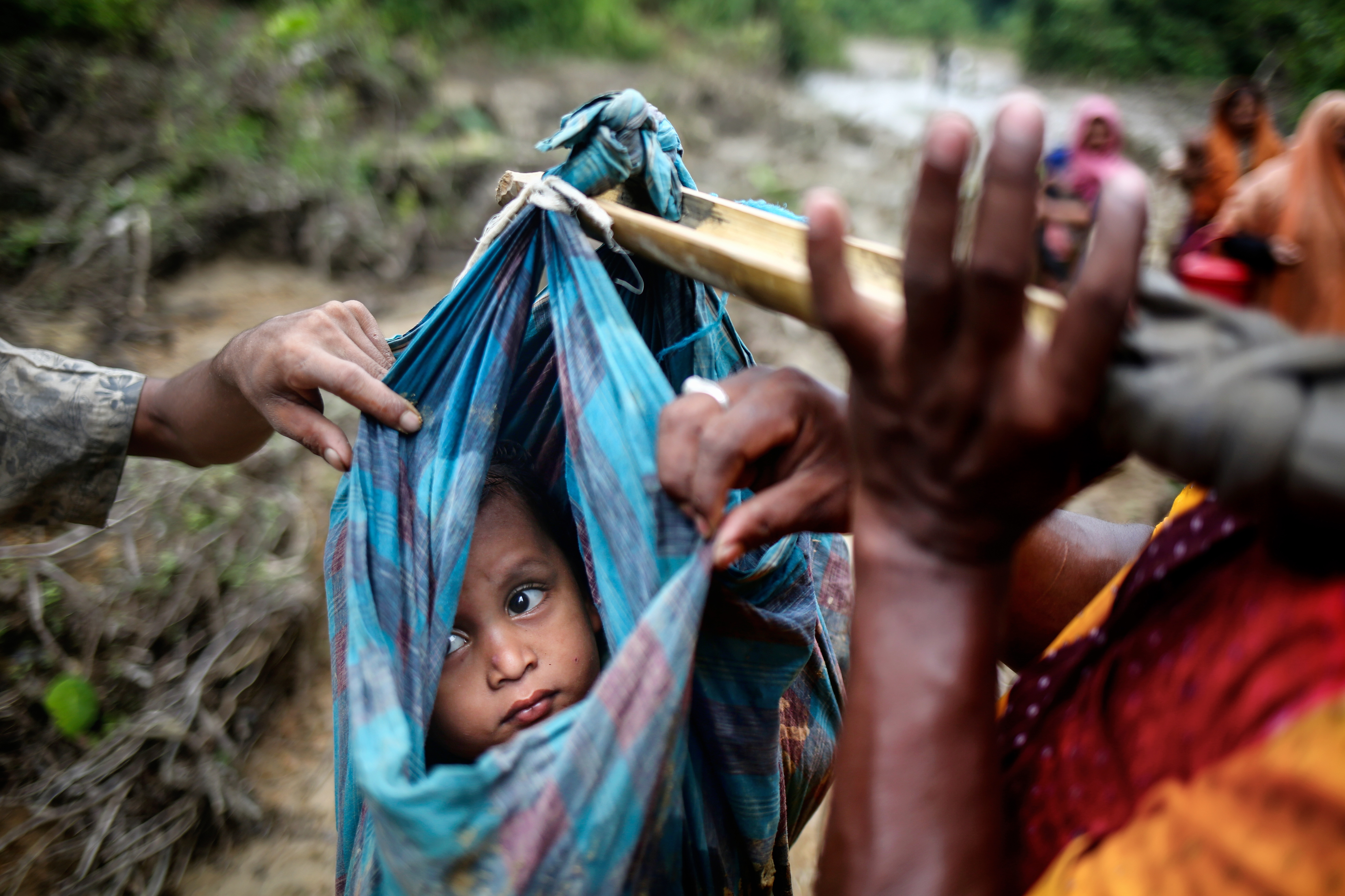 A Rohingya child looks up at the sky as they cross into Bangladesh from Myanmar