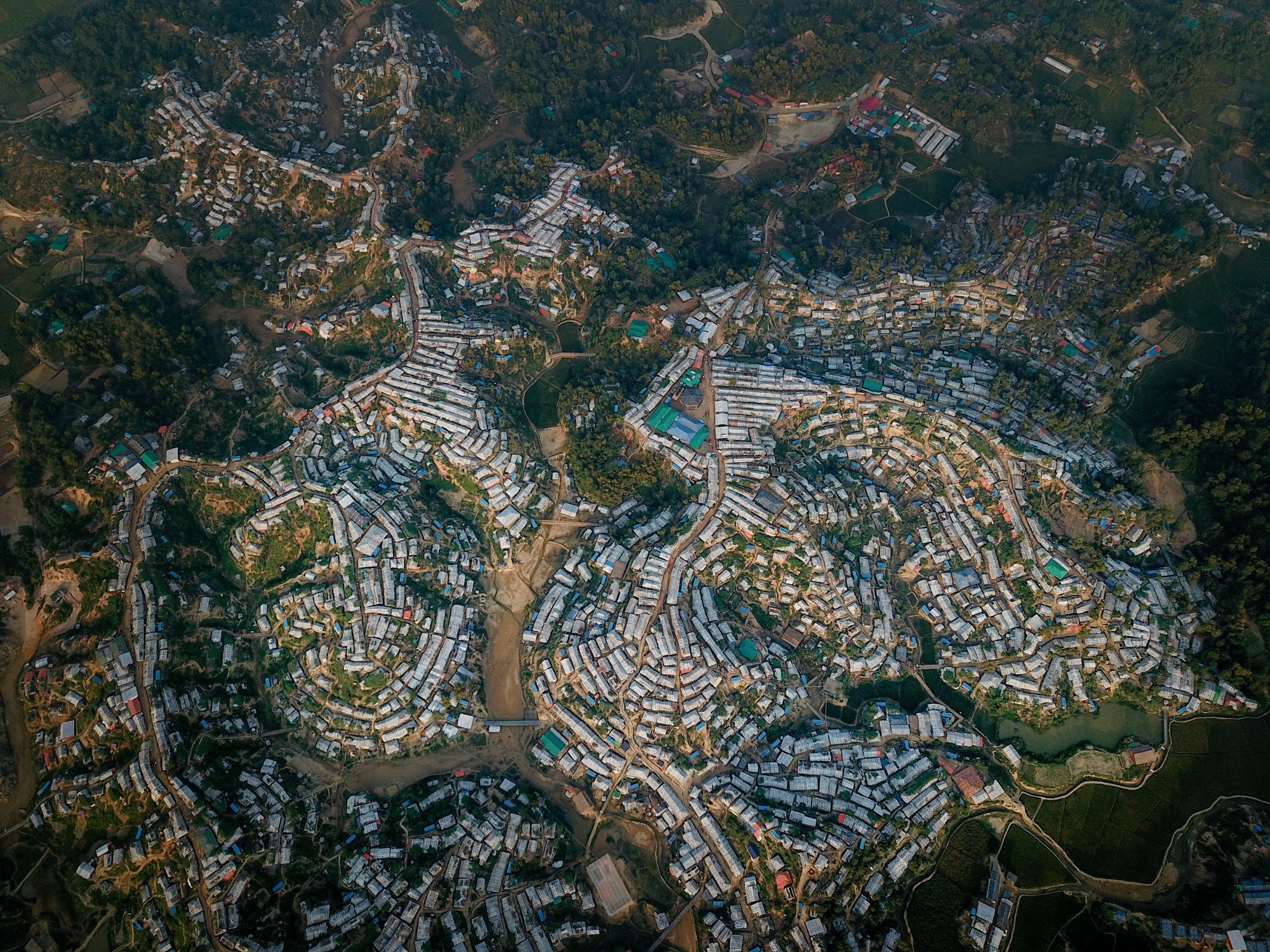 Bird's eye view shows Rohingya refugee camps with rows of houses with paths between them bordered by forests