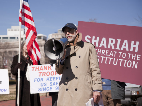 man wearing beige overcoat with hat and microphone at a rally