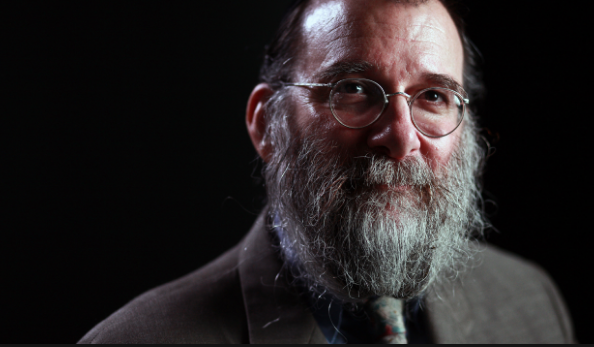portrait of a man, spectacled and bearded, staring in to the camera