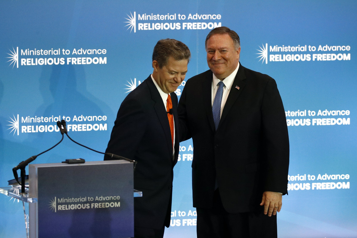 "Sam Brownback and Mike Pompeo smile while embracing in a side-hug. In front of them is a podium and behind them is a blue banner with logos that read, ""Ministerial to Advance Religious Freedom."""