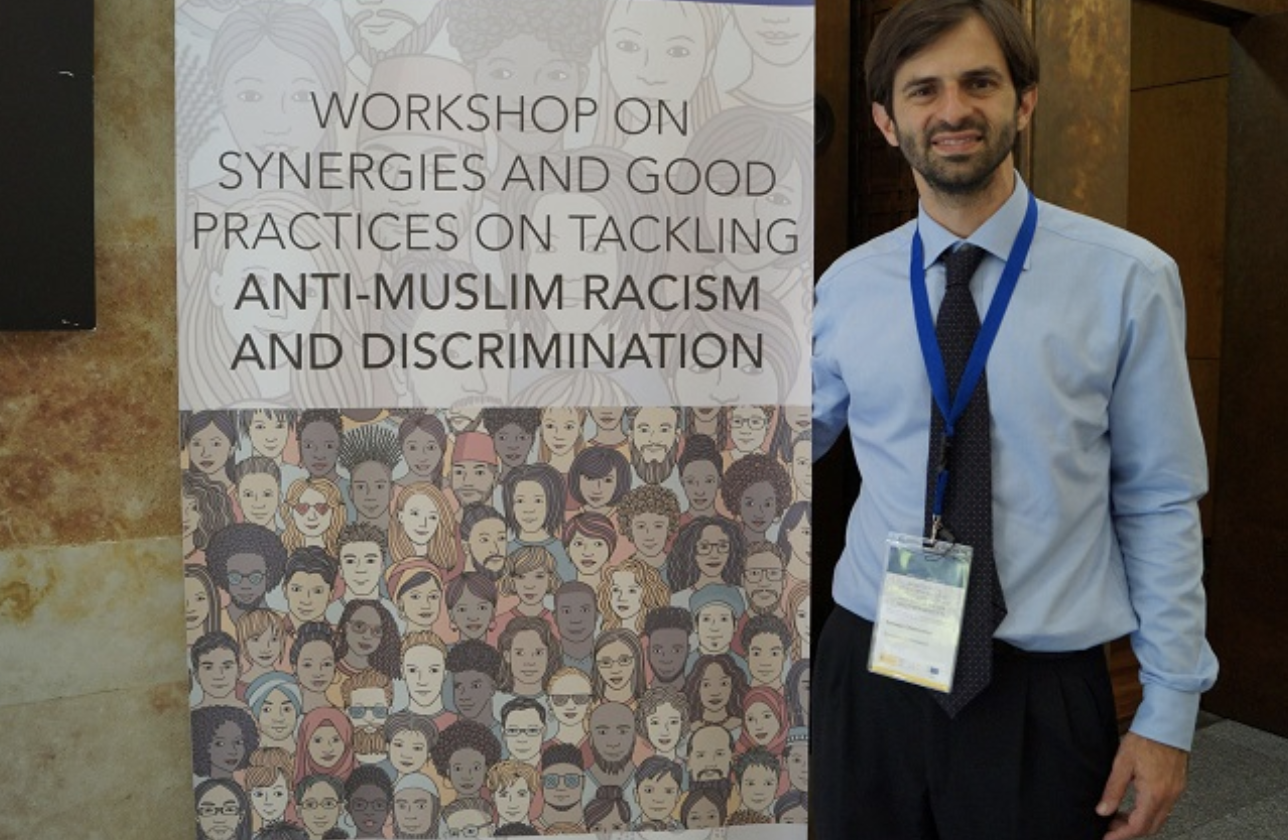 Tommaso Chiamparino stands in front of a sign. He is the coordinator on combating anti-Muslim hatred appointed by the European Commission.