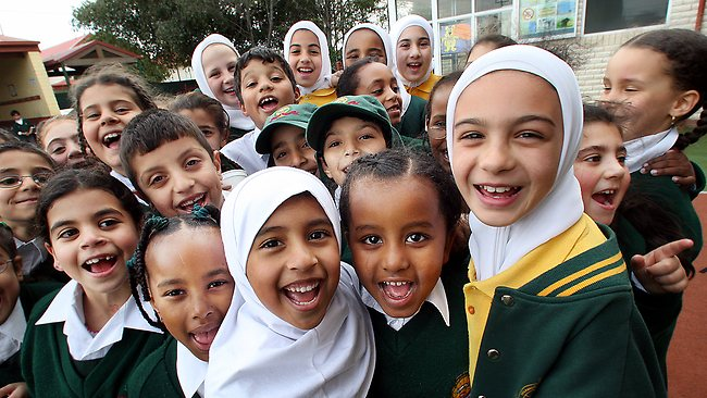 A group of children look at the camera and laugh. Some are wearing hijabs